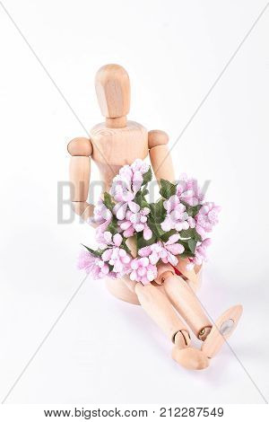 Wooden dummy sitting with flowers. Human wooden mannequin with pink artificial bouquet of flowers isolated on white background. In expectancy of beloved. Surprise and greeting concept.