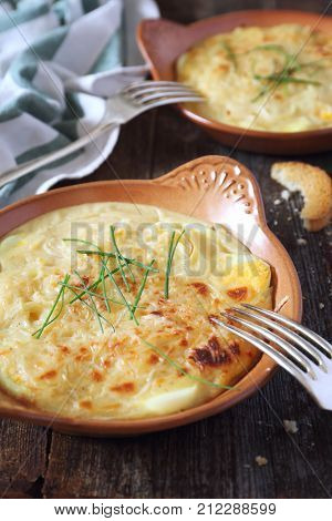 French cuisine. Eggs and onions with bechamel sauce and cheese rustic style