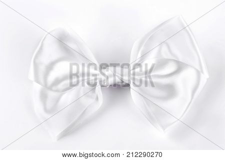 White bow tie on white background. White accessory for girls hair isolated on white background.