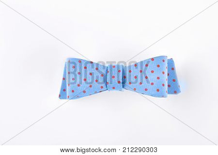 Blue dotted bow tie on white. Beautiful blue bow tie with red spots isolated on white background. Girls hair accessory.