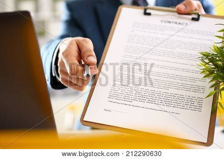 Male arm in suit offer contract form on clipboard pad and silver pen to sign closeup. Strike a bargain for profit white collar motivation union decision corporate sale insurance agent concept