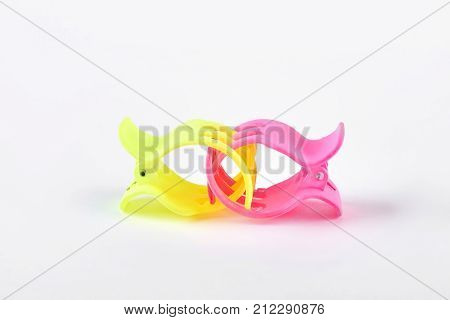 Two colorful hair clips on white background. Little yellow and pink hair claw isolated on white background. Child hair clamps.