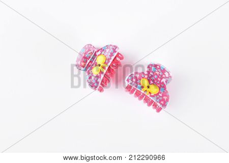 Pair of plastic patterned hair clips. Little pink hair claws with yellow bow isolated on white background.