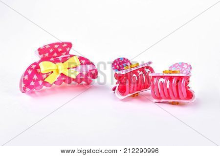 Pink plastic hair clips. Kids cute pink hair clips with yellow bow on white background. Little girls hair accessories.