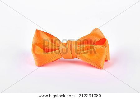 Yellow bow tie on white background. Beautiful accessory for girls hair isolated on white bakground. Kids elegant hair accessory.