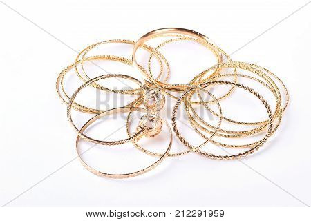 Golden bracelets and jewelry, white background. Beautiful female golden wrist bands isolated on white background. Indian bracelets over white.