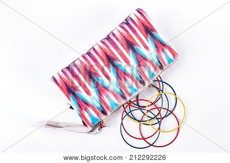 Glamour cosmetics bag and colorful bangles. Fashion toiletry bag with plastic colored bracelets on white background, top view. Woman stylish accessories.