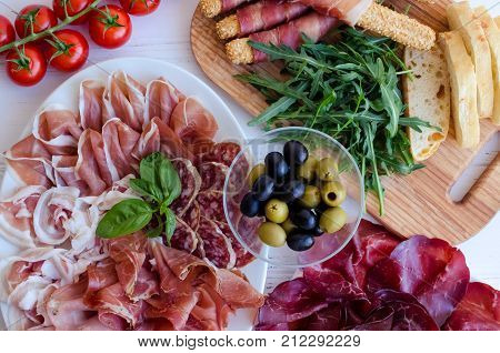 Table full of mediterranean appetizers tapas or antipasto. Assorted Italian food set. Delicious snack on party or picnic time. Chopping board with meat. Italian style banquet. Top view.