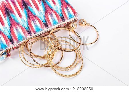 Golden bracelets and colorful pouch. Glamour cosmetics case and golden bracelets on white background. Female fashion accessories.