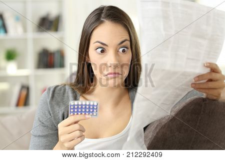 Confused Girl Reading Leaflet Of Contraceptive Pills