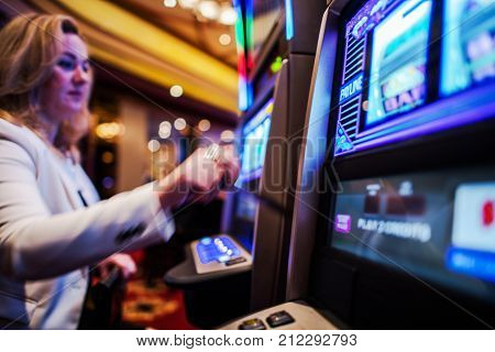 Casino Slot Games Play. Caucasian Woman in Her 30s Playing Slot Machine in the Casino.