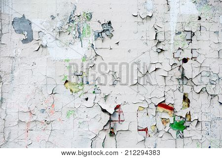 Abstract background of a rough peeling cracked paint on a tile. Wall of small tiles in white paint with cracks.