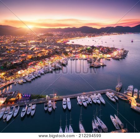 Aerial view of boats and beautiful city at sunset in Marmaris Turkey. Amazing landscape with boats in marina bay sea city lights mountains sky clouds. Top view from drone. Harbor with yacht