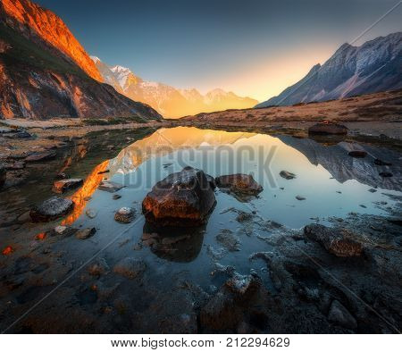 Wonderful landscape with high rocks with illuminated peaks stones in mountain lake reflection blue sky and yellow sunlight in sunrise. Nepal. Amazing scene with Himalayan mountains. Himalayas