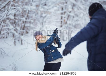 Snowball fight. Winter couple having fun playing in snow outdoors. Young joyful couple