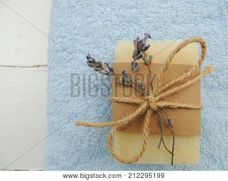 Handmade spa lavender soap on blue terry towel and vintage wooden background. Soap making. Soap bars. Spa, skin care.