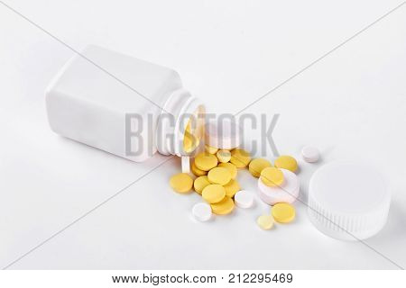 Yellow pills and white bottle. Vitamin pills and white plastic container, white background.