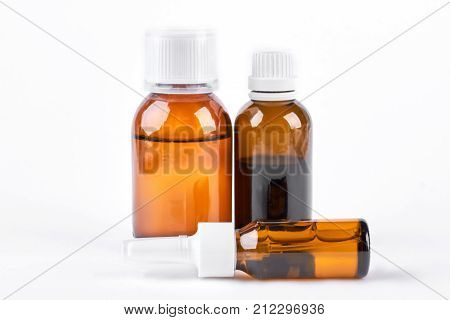 Bottles with medicine, nasal spray. Cough syrup, antipyretic syrup and nose drops on white background. Medication for cold treatment.