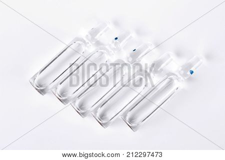 Raw of ampoules with liquid for injection. Break-seal glass ampules with medicine liquid on white background.