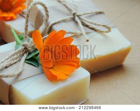 Handmade spa soap with calendula flowers on dark background. Soap making. Soap bars. Spa, skin care.