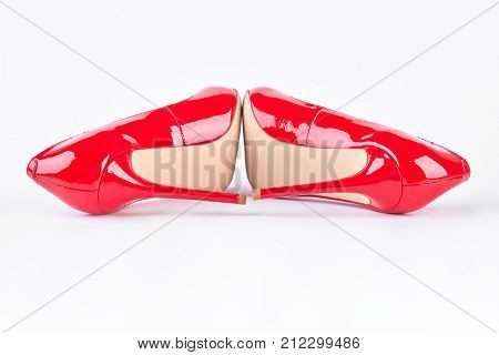 Woman beautiful red high heels. New classic shoes of red color with high heels on white background. Female elegance and sensuality.