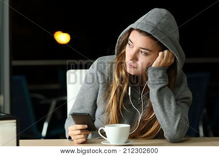 Sad pensive teenager listening to music in a bar in the night and looking at side