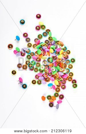 Many colorful push pins, white background. Isolated pile of colorful push pins. Heap of multicolored push pins on white background, top view.