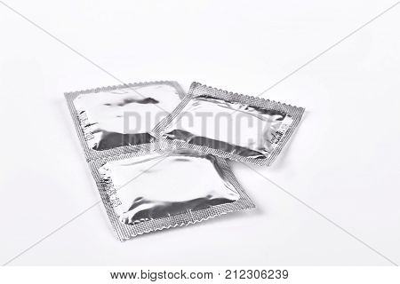 Condoms in silver package. Three contraceptives wrapped in silver packages. Latex protection against aids and infections.