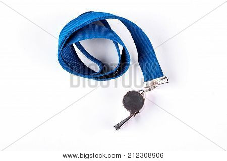 Whistle with blue rope, white background. Sport coach metal whistle isolated on white background, top view. Coach gym whistle.