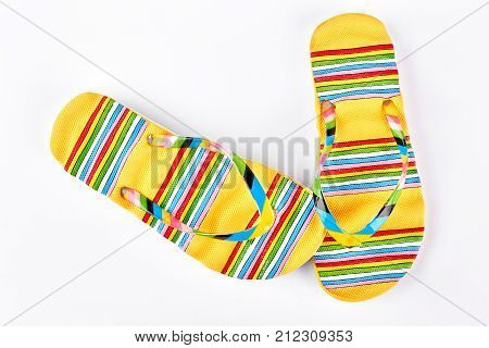 Female yellow patterned flip flops. Woman beautiful flip flops for vacation on white background, top view.