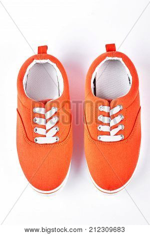 Female orange vans, top view. Textile orange and white gumshoes isolated on white background. High quality shoes on sale.