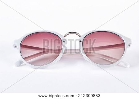 Round sunglasses with white rim. Fashion sunglasses with red glass and white plastic rim isolated on white background. Female fashion accessory.