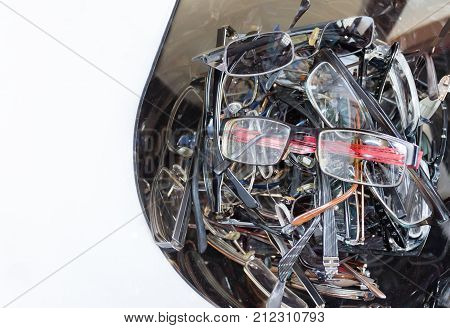 horizontal image of a whole pile of used eye glasses on one side of the image with room for text on the other side of image.