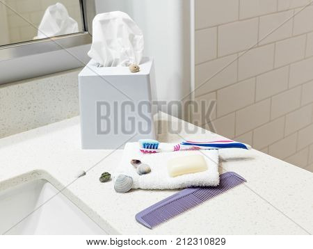 horizontal close up image of Kleenex in a container with a tooth brush and some hand soap and a purple comb lying on a white bathroom vanity decorated with a few sea shells