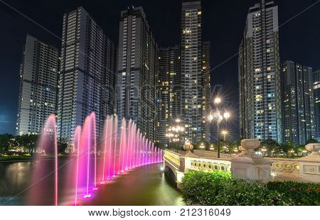 Ho Chi Minh City, Vietnam - November 30th, 2017: A state of the art fountain at night with colorful lights shimmering, behind the skyscrapers in the urban park development in Ho Chi Minh City. Minh, Vietnam