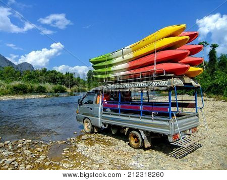 Tuk-tuk loaded with kayaks at Nam Song River near Vang Vieng Laos. Kayaking is a popular tourist activity in Vang Vieng.