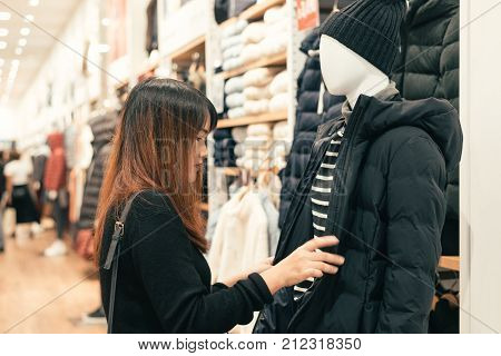 Half body shot of a happy asian young woman with shoulder bag looking at clothes hanging on the rail inside the clothing shop. Shopping fashion style and people woman concept.