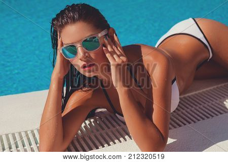 Beautiful tanned young woman with perfect body wearing white bikini and sunglasses relaxing near swimming pool. outdoor shot. copy space.