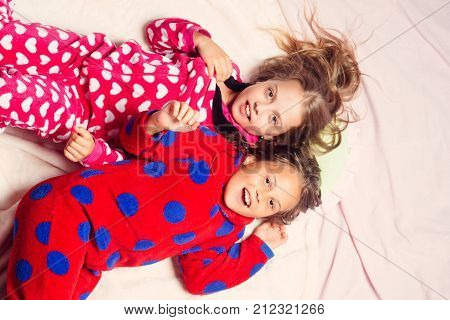 Girl sisters in pajamas happy smile in bed top view. Children nightwear fashion. Bedtime slumber dream sleepover. Childhood family love friendship. Comfort home concept.