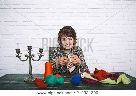 Pension and retirement old age. Granny character at Christmas eve. Needlework and knitting hobby. happy old lady or grandmother with needle and yarn. Old woman knitting socks from colorful thread.