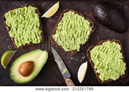 Healthy avocado toast. Mashed avocado on whole grain rye bread on dark background. Top view vegan food