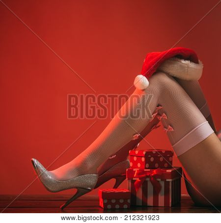 New Year Legs On Red Background With Present.