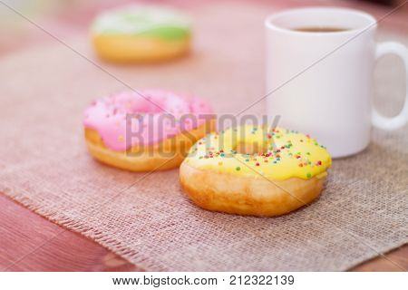Donuts with icing on the table. Nearby is a mug with coffee. Sweet colored donuts.