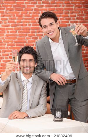 Young men in suits drinking in a wine bar