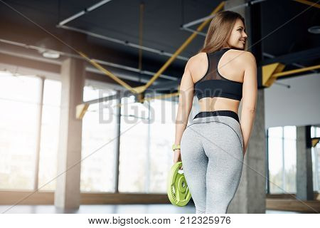 Young fitness trainer holding a dumbell disc exercising abl and buttocks.