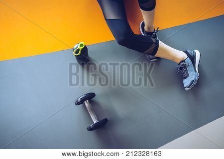Woman excercise workout in gym fitness breaking relax holding apple fruit after training sport with dumbbell and protein shake bottle healthy lifestyle bodybuilding Top view