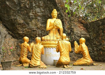 Statue Gold sitting buddha surrounded by monk Phou Si Hill Luang Prabang Laos