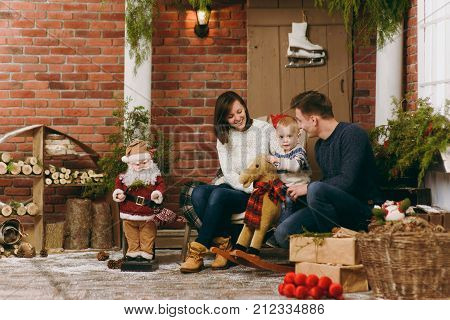 Young Happy Parents With A Cute Little Child Boy On Rocking Horse, Dressed In Sweater In Decorated N