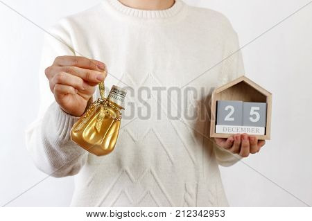 Female hands holding Christmas gift box with dollar and calendar xmas. 25 Desember. background. Holiday gift and decoration.