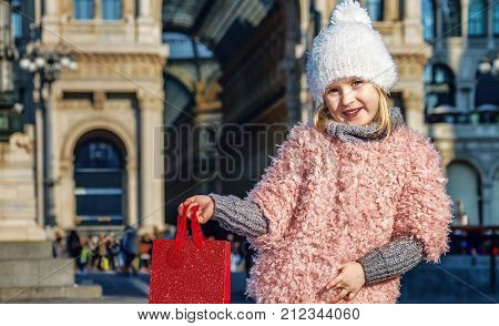 Rediscovering things everybody love in Milan. Full length portrait of happy elegant child showing red shopping bag in Milan Italy
